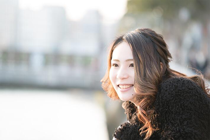 遠くを見て微笑む女性